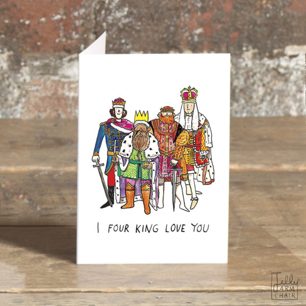 A card stood on a wooden table. On the card, four kings in various coloured robes are all standing together. Text: I four king love you'.