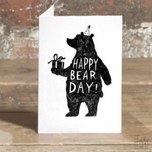 A card on a wooden table. On the card a black silhouette of a bear wearing a party hat and holding a present. Inside the bear in white writing it says 'Happy Bear Day!'.