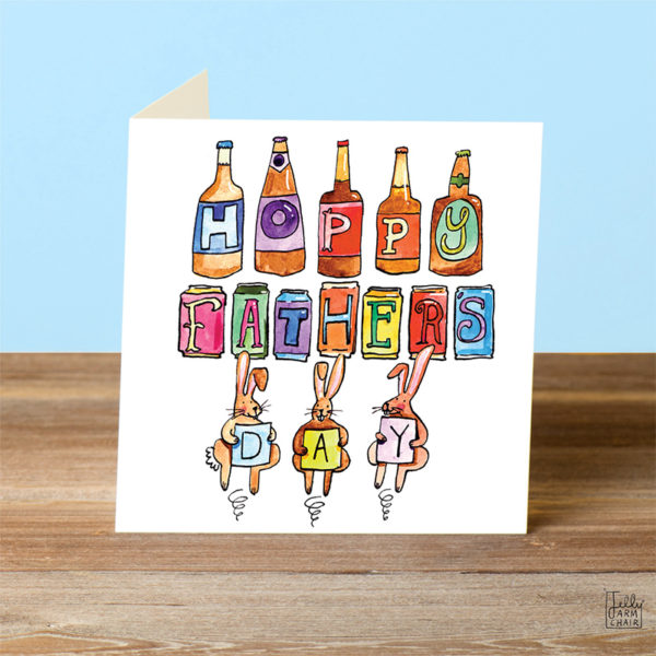 A card on a wooden table. On some different coloured beer bottles and cans are some letters spelling 'Happy Father's' and then three rabbits are bouncing and each holding a letter to spell 'day'.