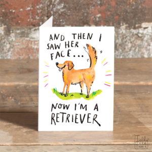 A card on a wooden table. On the card a golden retriever surrounded by pink and yellow lines. Text above reads 'And then I saw her face' Text Below reads 'Now I'm a retriever'