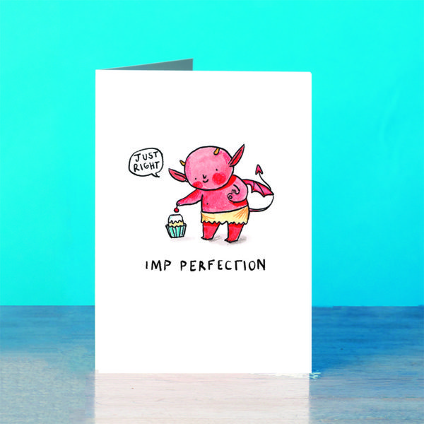 A blue background and a grey wooden table. On the table is a card. A little red imp with orange horns putting a cherry on the top of a cupcake in a blue case. The imp is saying 'Just right'. The text below reads 'Imp Perfection'.