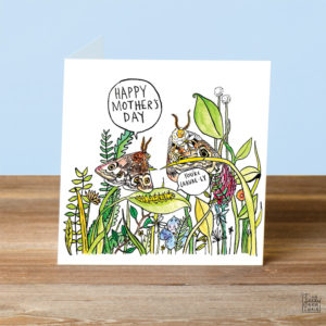 A card on a wooden table. On the card are two moths perched on the stems of some colourful flowers, one small moth is saying 'Happy Mother's Day' and a caterpillar is saying 'You're Larvae-ly'.