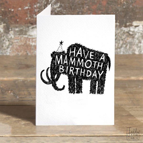 A card on a wooden table. On the card a black silhouette of a mammoth wearing a party hat. Inside the mammoth is white writing it says 'Have a mammoth birthday'