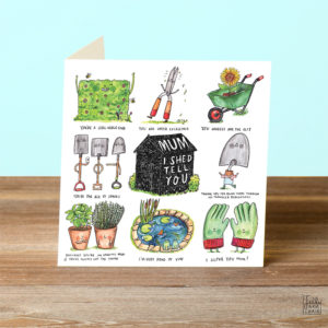 A card on a wooden table. On the card a black shed in the centre of the card. In white on the shed is written 'Mum I Shed Tell You'. Surrounding this are eight illustrated gardening puns.