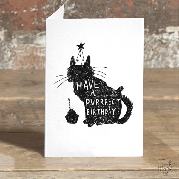 A card on a wooden table. On the card a black silhouette of a cat with a party hat and a cupcake, inside the can in white it says 'Have a purrfect birthday'.