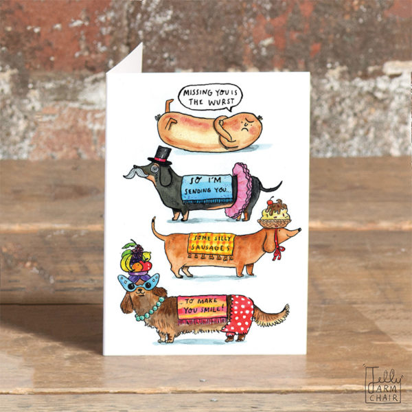 A card with a blue envelope inside. There are three sausage dogs in fancy dress and a sausage on the card. The text bubble above the sausage reads 'Missing you is the wurst. The text on the dogs clothes reads 'So I'm sending you some silly sausages to make you smile'