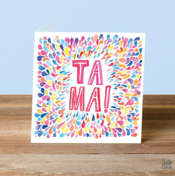 A card on a wooden table. On the card lots of teardrop shapes of all different colours are shimmering outwards, inside in pink and white it says 'Ta Ma!'.