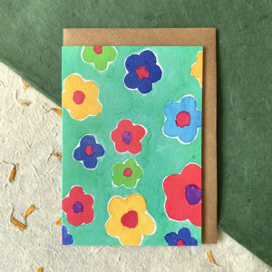 A card with a turquoise back ground. Printed on this background are multicoloured daisies.