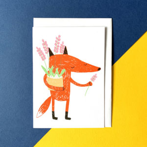 A fox holding a pot of pink flowers