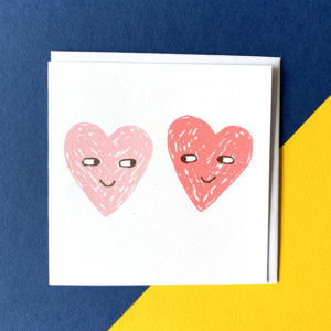Two hearts with eyes looking at one another. one is a slightly darker shade of pink .