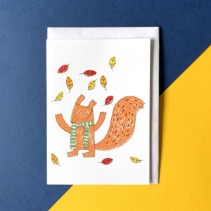 A squirrel wearing a green scarf surrounded by falling autumn leaves